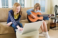 View of two sisters sitting on sofa with a laptop and a guitar