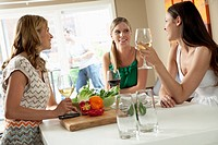 Three women have a conversation over wine.