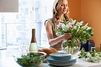 Woman arranges flowers on a counter.