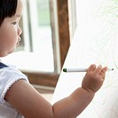 Young girl uses markers to color on an easel.
