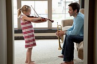 A young girl is playing the violin while her father holds a trumpet.