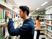 female and male college students choosing textbook from shelves in library. Horizontal shape, side view, waist up, focus on foreground