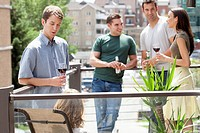 Group of friends socialize on an outdoor patio with alcohol.
