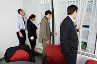 View of businesspeople peeping through windows in the office