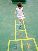Four year old girl playing hopscotch in a children's playground