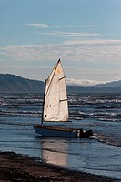 A sailing boat left alone on the beach.