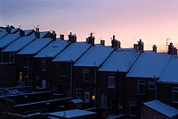 Aerial view of row housing, Newton Cap Bank, Bishop Auckland, Northern England, with pink sky, snow on line of rooftops, some windows illuminated, at ...