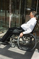 Side profile of a mid adult man sitting in a wheelchair