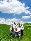 Multi_generational family standing in field