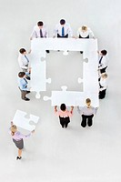 Business people forming square with jigsaw pieces