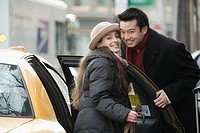 Portrait of a young couple smiling together near a taxi