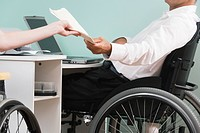 Mid section view of a mid adult man sitting in a wheelchair and doing home finances