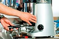 Barista prepares espresso in his coffeeshop, close_up