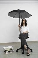 Woman sitting in a room holding an umbrella.