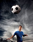 football player looking at flying ball against a stormy sky
