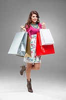 studio portrait of a beautiful young woman, in a colourful outfit, holding in her hands a few shopping bags. she is hopping on one foot, laughing and ...