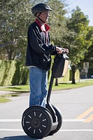 Side profile of a senior man riding a segway