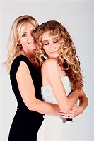 beautiful real couple mother in her 40s and teenage daughter wearing evening wear and make_up in studio