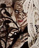 beautiful young woman with red lips looking from behind antique lace curtain with lace shadows on her face over grunge scratched background
