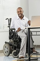 Portrait of a businessman with Cerebral Palsy sitting in a wheelchair and working on a computer with his foot