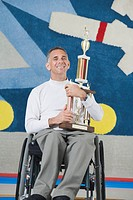 Portrait of a disabled mature man holding a trophy and smiling