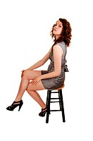 An lovely young woman, sitting on a chair in high heels and holdingher head high up, for white background.