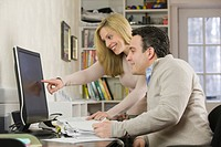 Businesswoman with a Hispanic businessman working on a desktop pc