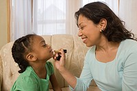 Hispanic woman applying lipstick on her daughters lips