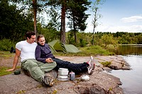 A couple camping and eating outdoors