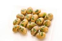 gruene Oliven auf einem weissen Teller