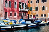 Bright blue and white laden barge moored in front of red and yellow palazzi, with single woman in pink walking alongside canal, sunny autumn morning i...