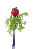 Cherry tomato and lettuce on a fork isolated on white