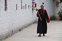 Pilgrim with a prayer wheel in front of the Potala Palace, UNESCO World Heritage Site, Lhasa, Tibet, Asia