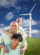 Happy African American Family and Wind Turbine with Dramatic Sky and Clouds.