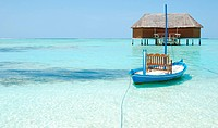 beautiful seascape with honeymoon villa in Maldivian Island and typical boat