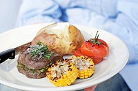 A person holding a plate of grilled beef medallions, a jacket potato and grilled tomatoes and corn on the cob