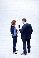 Businessman and businesswoman standing with cell phone outdoors