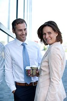 Businessman and businesswoman with coffee to go talking