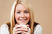 Photo of a smiling female holding a coffee, hot chocolate, or tea.