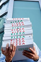 Man with pizza boxes in front of his face