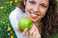 Young attractive woman holding a fresh apple in nature
