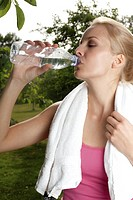 Blond young woman drinking water from bottle