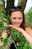 Portrait of beautiful smiling woman behind the tree branch