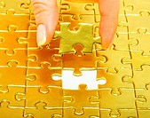 woman fingers holdings gold puzzle