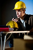 Closeup of young male construction worker talking on walkie_talkie