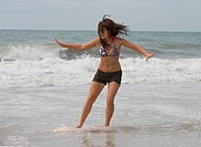 Athletic teen girl skimboarding in the surf of the Atlantic Ocean at Emerald isle, North Carolina. Skimboarding is a fairly new activity somewhat like...
