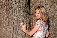 Beautiful girl smiles on background of the oak