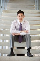 Businessman sitting on a stairway.