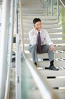 Businessman uses a cellphone on an office stairway.