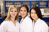 Three female scientists in the lab and smiling at the camera.